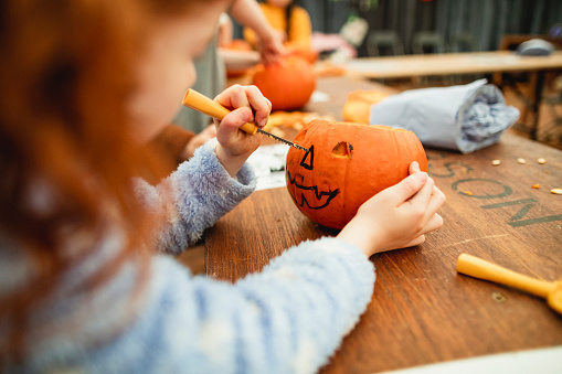 Family with children carving pumpkins at a farm after picking them at a farm in preparation for Halloween.