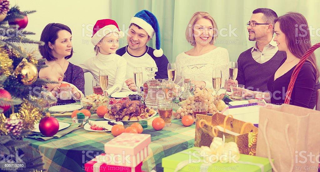 family celebrates Christmas at  table royalty-free stock photo