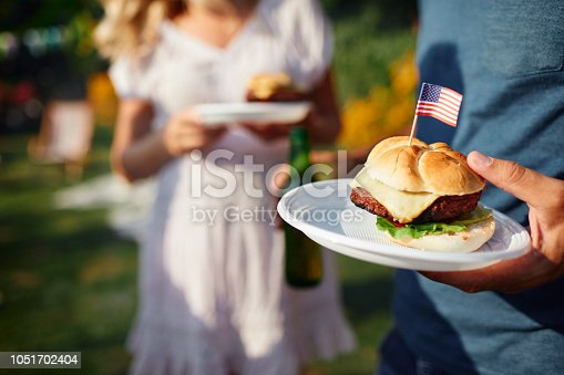 Family on picnic in back yard celebrating 4th of July - Independence Day. Focus on burger with USA flag.