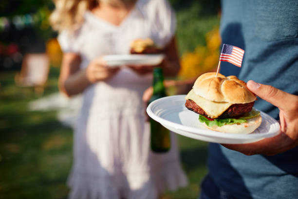Family Celebrating 4th of July Family on picnic in back yard celebrating 4th of July - Independence Day. Focus on burger with USA flag. happy 4th of july photos stock pictures, royalty-free photos & images