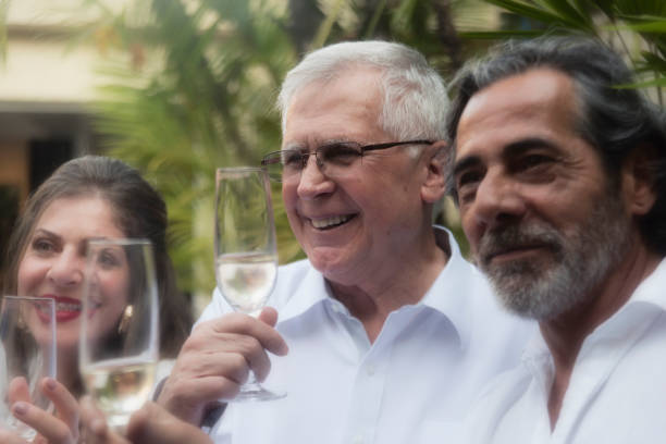 Family celebrating around grandfather Family celebrating New Year`s Eve in Brazil. Senior man at the center. reveillon stock pictures, royalty-free photos & images