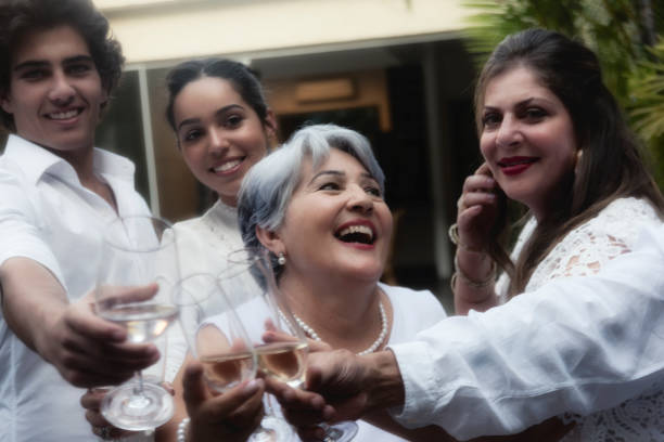Family celebrating around grandmother Family celebrating New Year`s Eve in Brazil. Senior woman at the center. Woman empowered. reveillon stock pictures, royalty-free photos & images