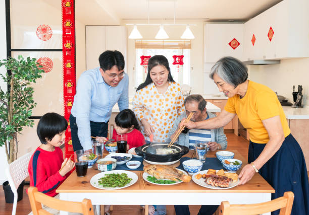 family celebrating chinese new year together - chinese new year stock pictures, royalty-free photos & images
