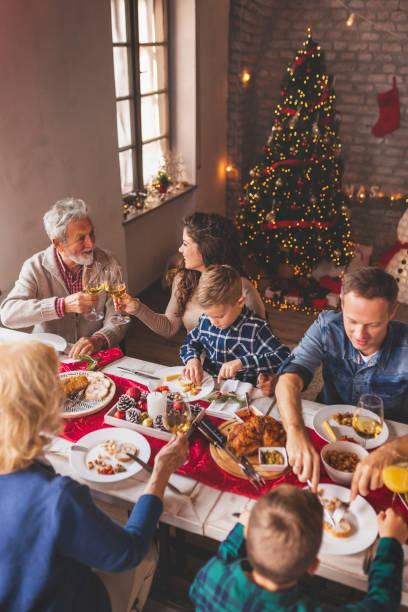 Family celebrating Christmas at home, having dinner stock photo