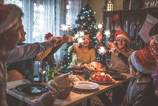 family celebrating christmas for many years together - family dinner stock photos and pictures