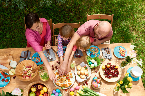 Top view of couple and their little daughters sitting at festive dining table with tasty homemade pastry, fruit and Easter eggs outdoors