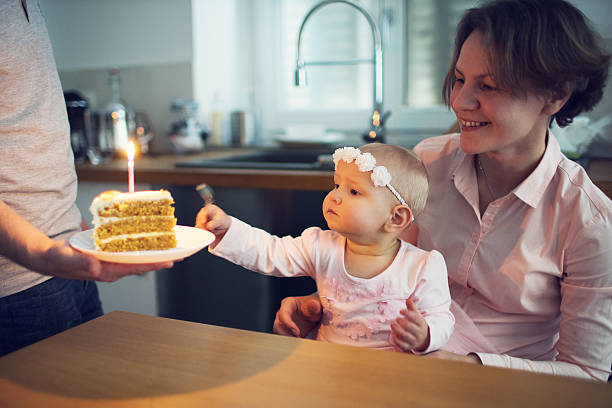Family celebrating first birthday at home stock photo