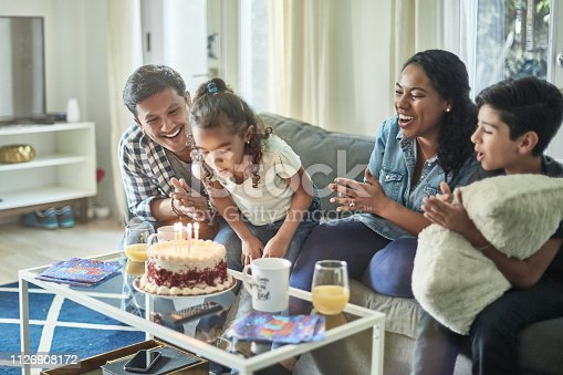 Girl blowing birthday candles while family clapping for her. Parents and children are sitting on sofa in living room. They are celebrating at home.