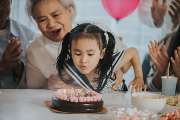 Family celebrating girl's birthday at home stock photo Thailand, Bangkok,Birthday, Family with one children, lifestyles, wishing, party, close- up, cute, horizontal birthday wishes for daughter stock pictures, royalty-free photos & images
