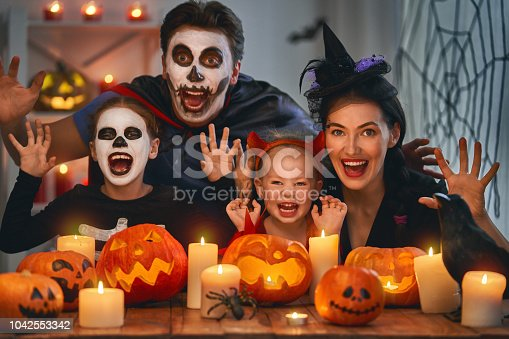 Mother, father and their kids having fun at home. Happy family celebrating Halloween. People wearing carnival costumes and makeup.