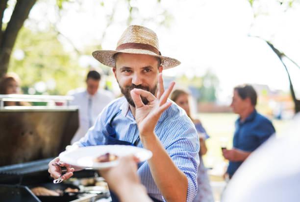familienfeier oder eine grillparty draußen im hinterhof. - grillschürze stock-fotos und bilder