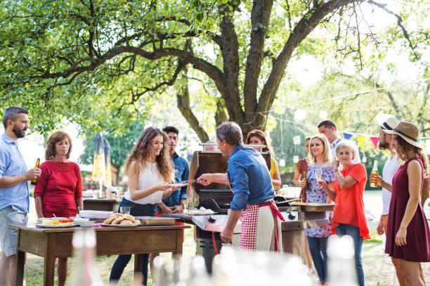 family celebration or a barbecue party outside in the backyard. - barbecue grill stock photos and pictures