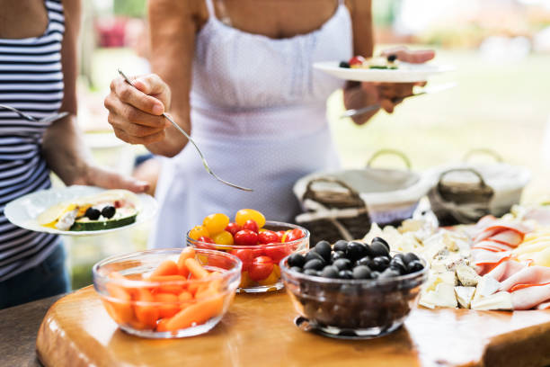Family celebration or a garden party outside in the backyard. Close up. Family celebration outside in the backyard. Big garden party. Unrecognizable people eating. Close up. olive fruit stock pictures, royalty-free photos & images