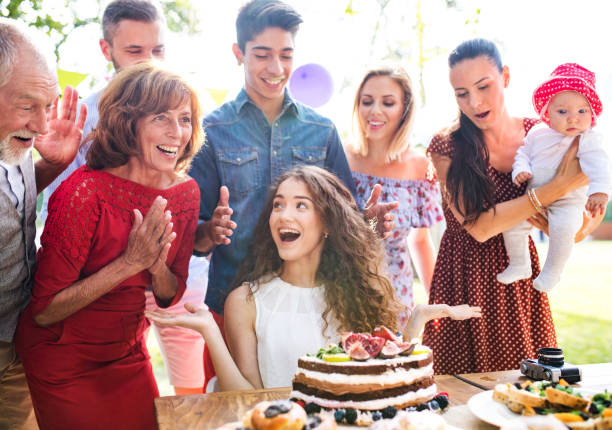 Family celebration or a garden party outside in the backyard. Family celebration outside in the backyard. Big garden party. Birthday party. A teenage girl with a birthday cake. birthday wishes for daughter stock pictures, royalty-free photos & images