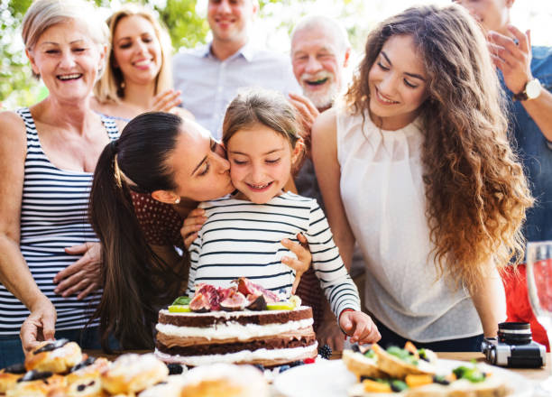 Family celebration or a garden party outside in the backyard. Family celebration outside in the backyard.Big garden party. Birthday party. Small girl with a birthday cake. group of friends giving gifts to the birthday girl stock pictures, royalty-free photos & images