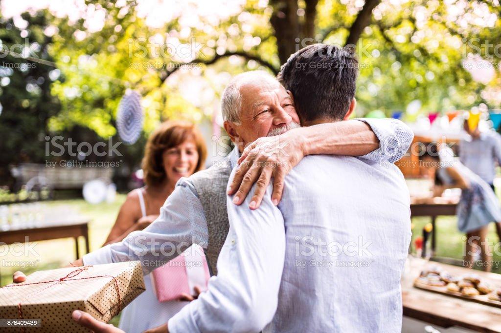 Celebración familiar o una fiesta en el jardín exterior en el patio trasero. - Foto de stock de Abrazar libre de derechos