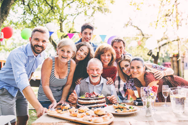 family celebration or a garden party outside in the backyard. - family meeting stock photos and pictures