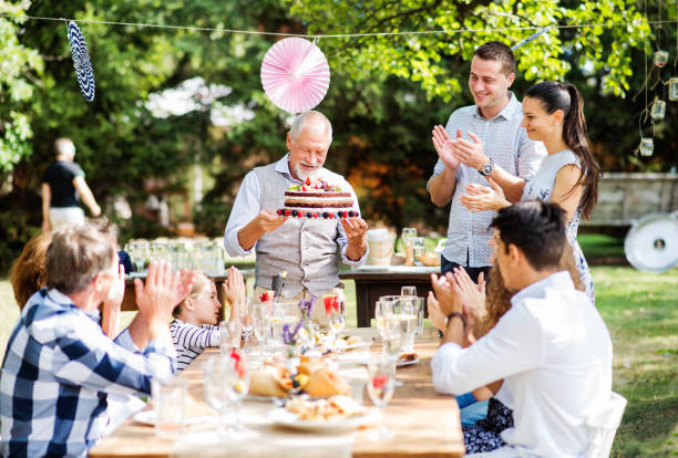 Family celebration or a garden party outside in the backyard. Family celebration outside in the backyard. Big garden party. Birthday party. A senior man holding a birthday cake. birthday wishes for daughter stock pictures, royalty-free photos & images