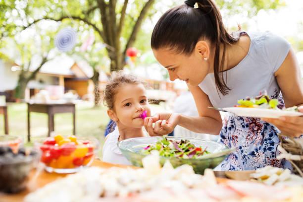 familienfeier oder eine gartenparty draußen im hinterhof. - partysalate stock-fotos und bilder