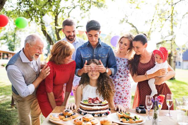 familienfeier oder eine gartenparty draußen im hinterhof. - jugendliche geburtstag geschenke stock-fotos und bilder