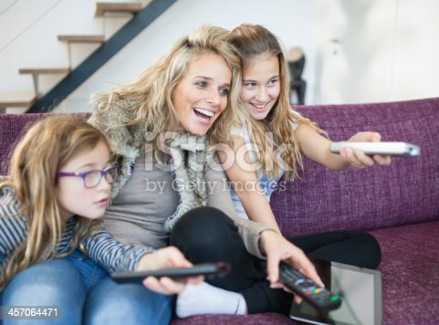 1134439364 istock photo Family changing channels on the television 457064471