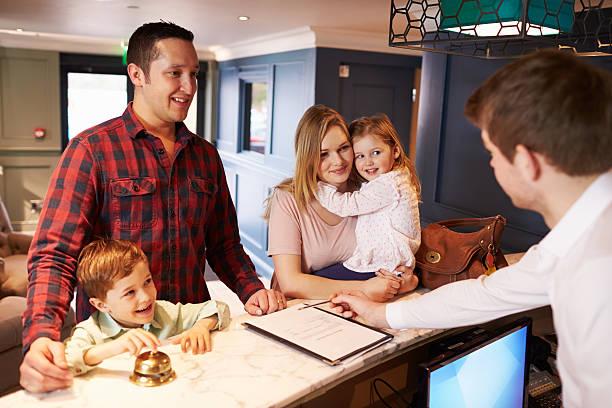 Família fazer o check-In na recepção do Hotel - foto de acervo