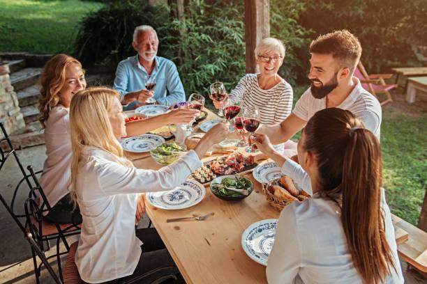 Familie jubelt über den Esstisch im Freien – Foto