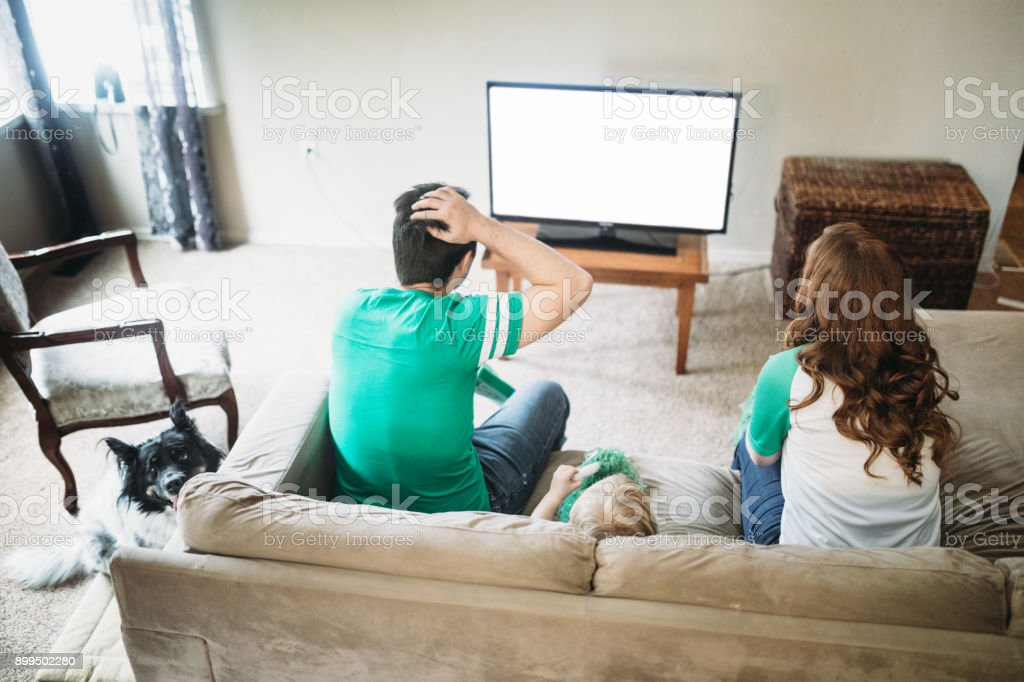 Family Cheering While Watching Football Game stock photo