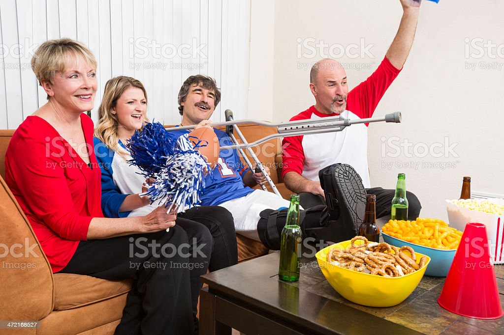 Family cheers for their team with injured viewer royalty-free stock photo