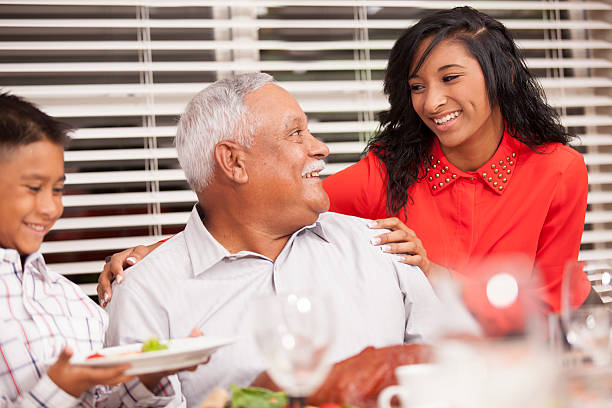 Family Child With Grandfather On Thanksgiving Day Dinner Table Stock Photo