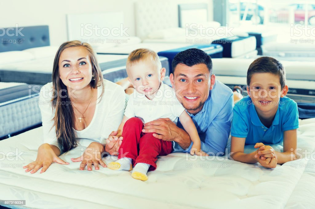 Happy family of four choosing right mattress in modern home...