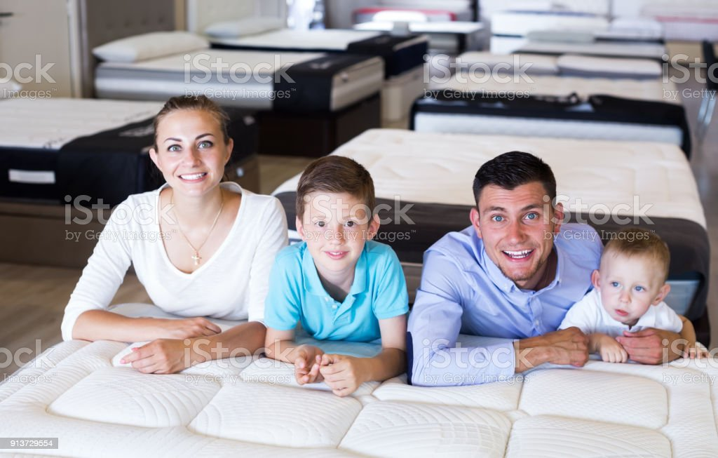 Smiling family of four selecting right mattress in modern home...