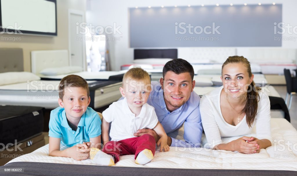 Glad family of four choosing right mattress in modern home...