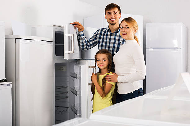 family choosing refrigerator in store - happy person buy appliances stock photos and pictures