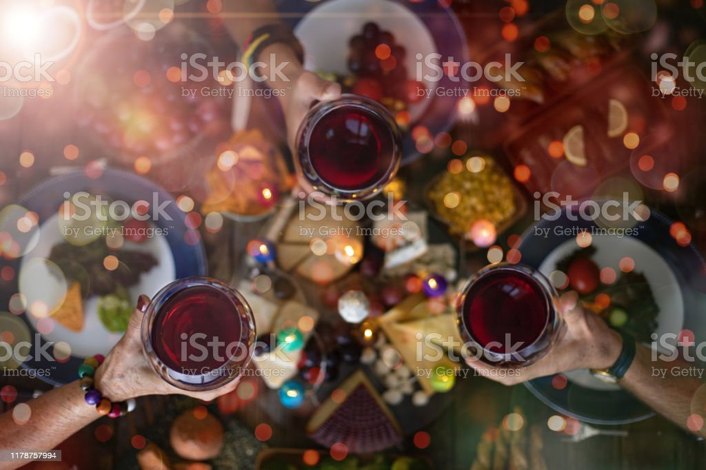 Family Christmas dinner for a celebration with red wine and cheers. - Foto stock royalty-free di Alchol