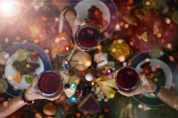 family christmas dinner for a celebration with red wine and cheers. - pranzo di natale foto e immagini stock