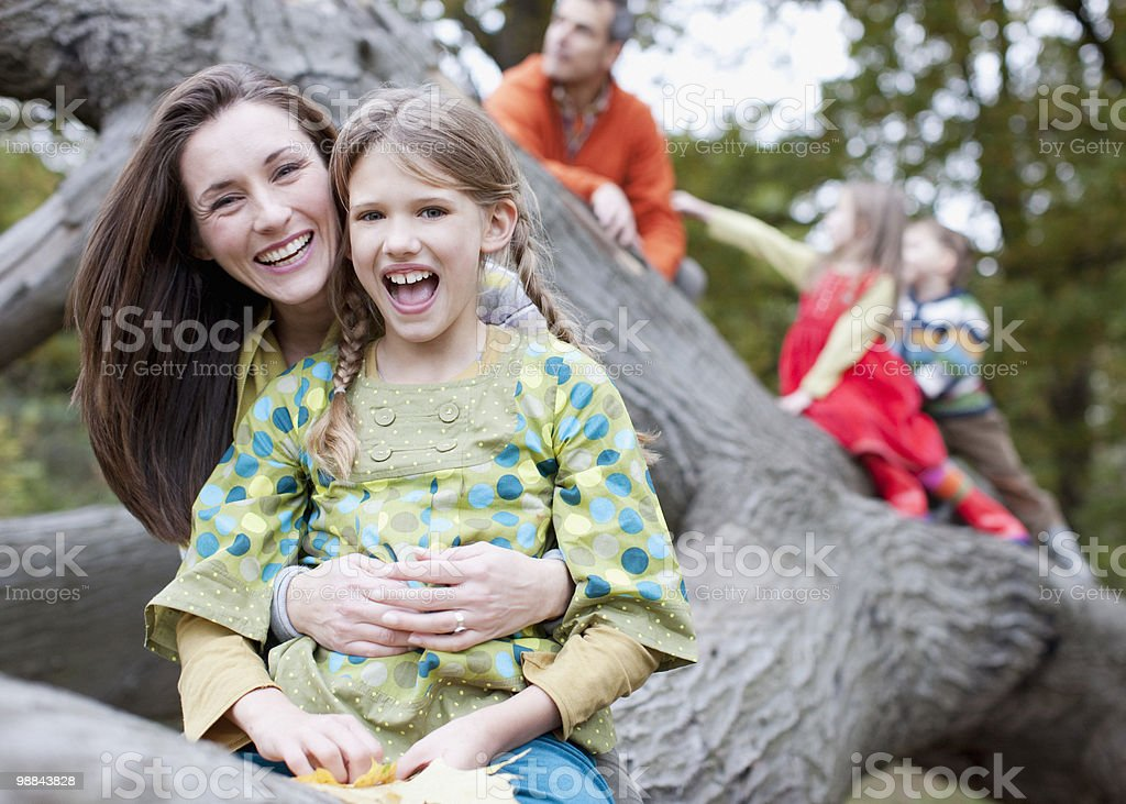 Family climbing on tree branch 免版稅 stock photo