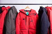 family concept or showroom of down jacket winter parka hanging on a hanger in the wardrobe