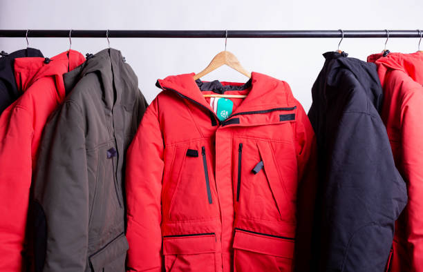 family concept or showroom of down jacket winter parka hanging on a hanger in the wardrobe - giacca foto e immagini stock