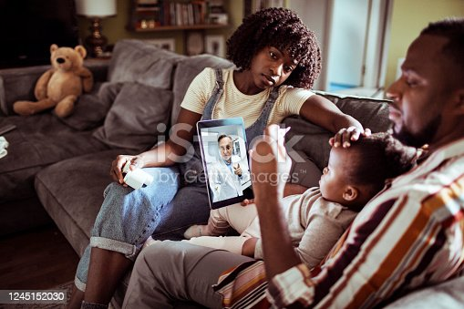 Close up of a young family consulting with their doctor over a digital tablet