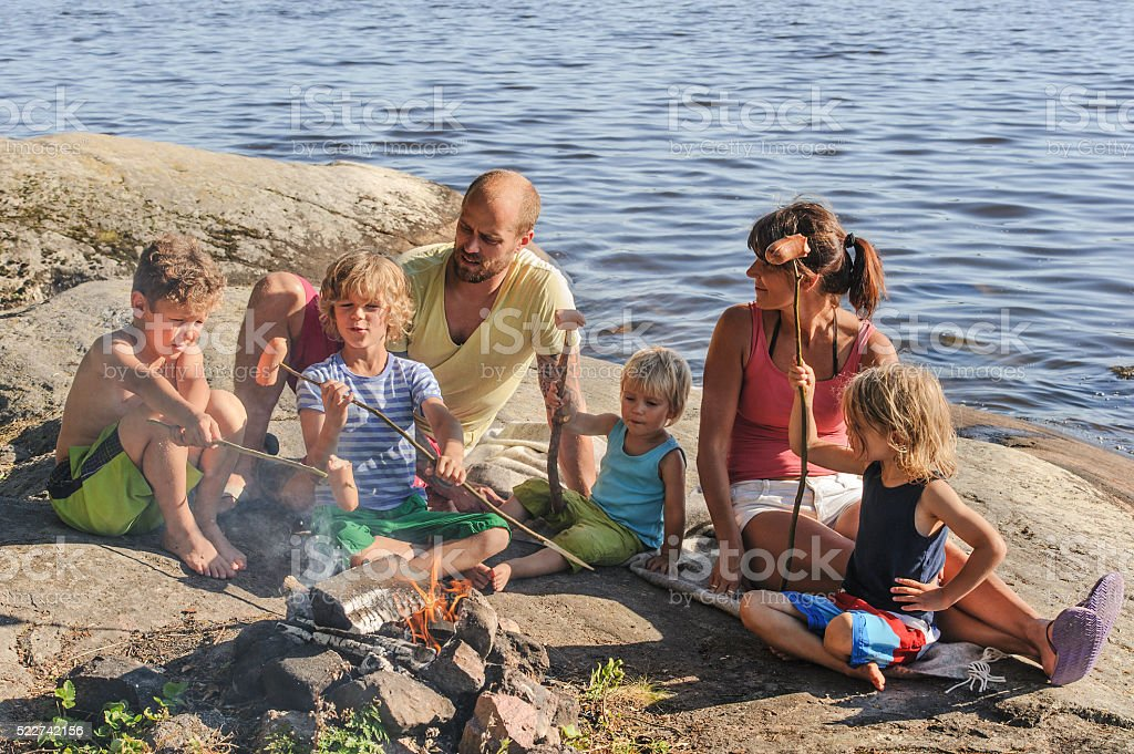 family cooking at campfire stock photo