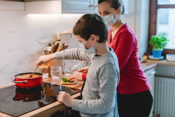 Family cooking at home during coronavirus crisis stock photo