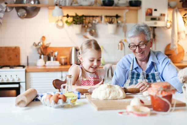 Family cooking at home. Grandmother and child have fun. Making italian food and meal in cozy kitchen stock photo