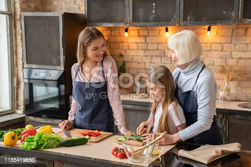 638984280 istock photo Family cooking food in kitchen 1155419850