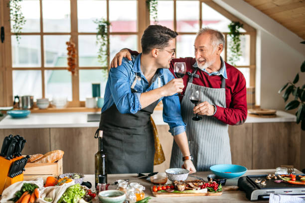 Family Cooking Lessons. Father and  Son Cooking in Kitchen stock photo