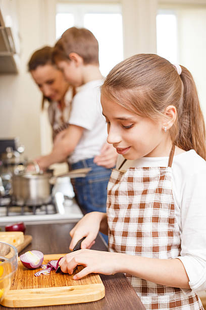 Family cooking. Mum and children in the kitchen Family cooking background. Young smiling teenage girl cutting onion. Mum and children in the kitchen sergionicr stock pictures, royalty-free photos & images