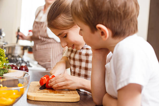 Family cooking. Mum and children in the kitchen Family cooking background. Sister and brother cutting tomato and mother having cooking there in the kitchen sergionicr stock pictures, royalty-free photos & images