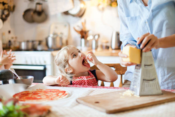 Family cooking pizza in kitchen. Mother and daughter preparing homemade italian food. Funny little girl gourmet is helping woman, eating and tasting cheese and ingredients. Children chef concept. stock photo