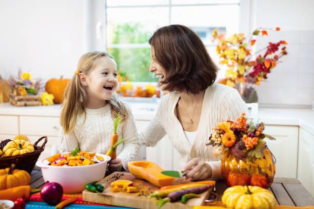 familie kochen kürbissuppe für halloween-mittagessen - fensterdeko herbst stock-fotos und bilder