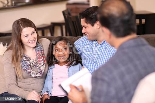 Multi-ethnic family at home with mental health professional, social worker, or family therapist.  Adopted child with young family.